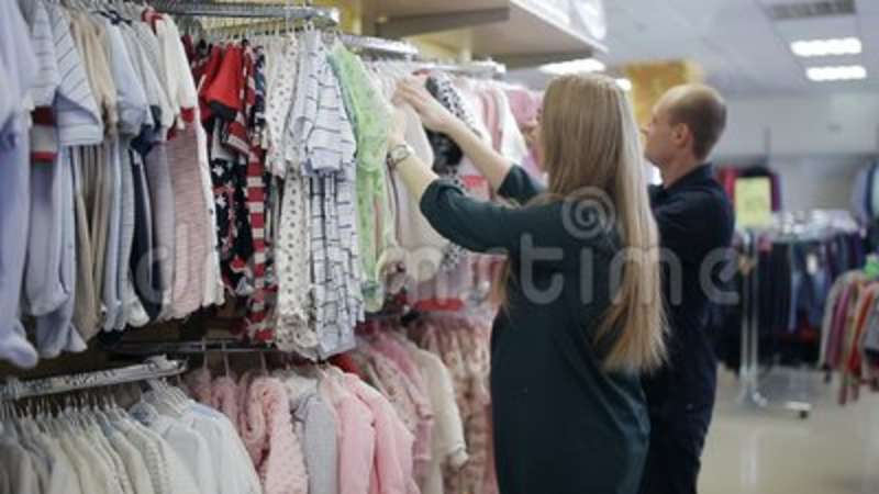 5b07fb8787f Young happy pregnant woman choosing newborn clothes at the baby shop store  stock footage video. Choice, girl.