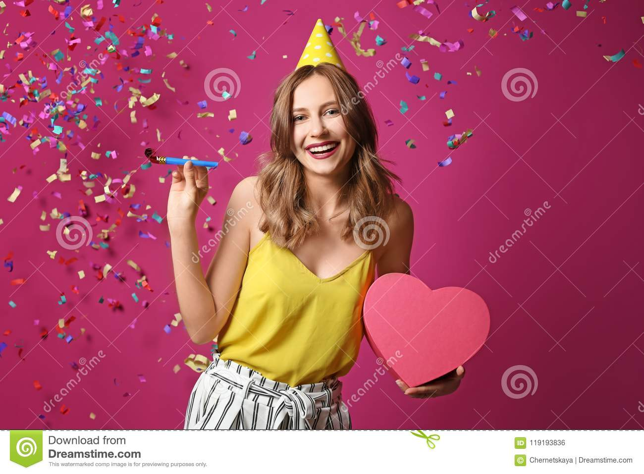 Young Woman With Birthday Gift And Party Blower On Color Background