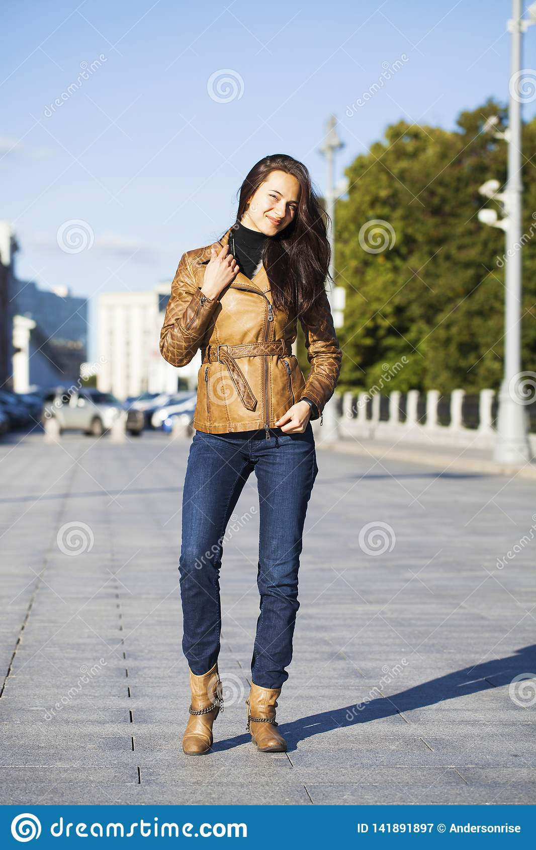 Young happy woman in brown leather jacket