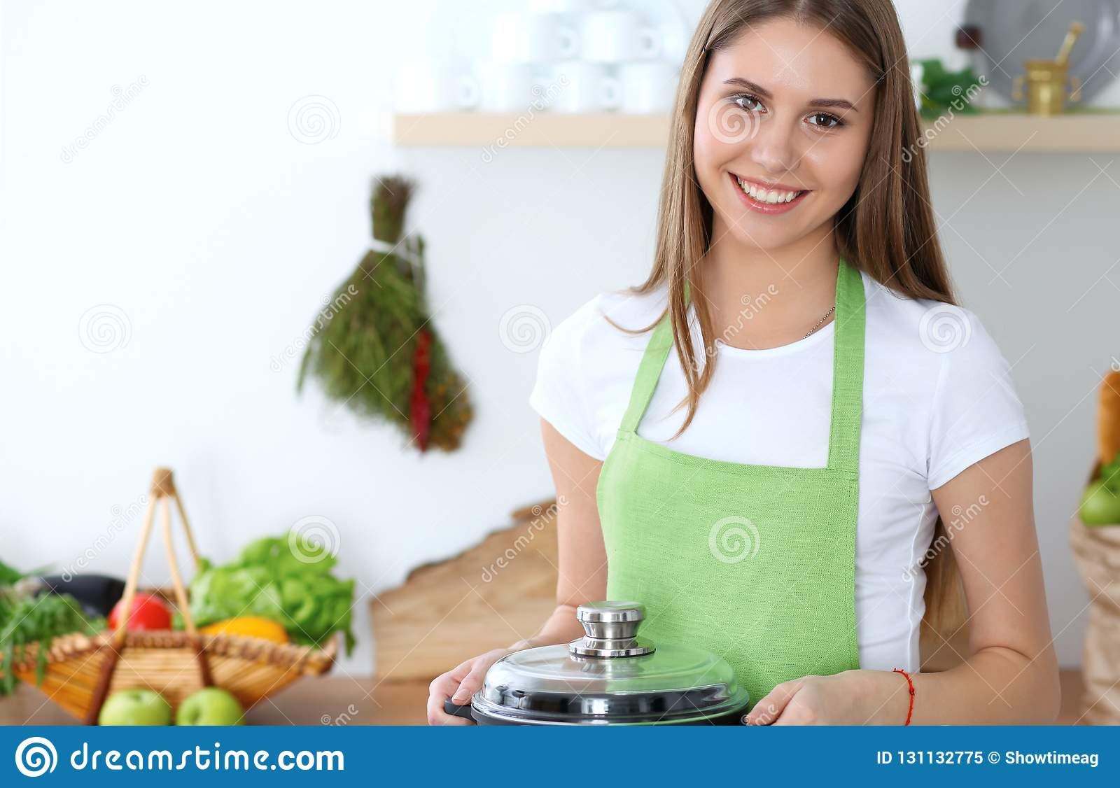 Young happy woman cooking soup in the kitchen. Healthy meal, lifestyle and culinary concept. Smiling student girl