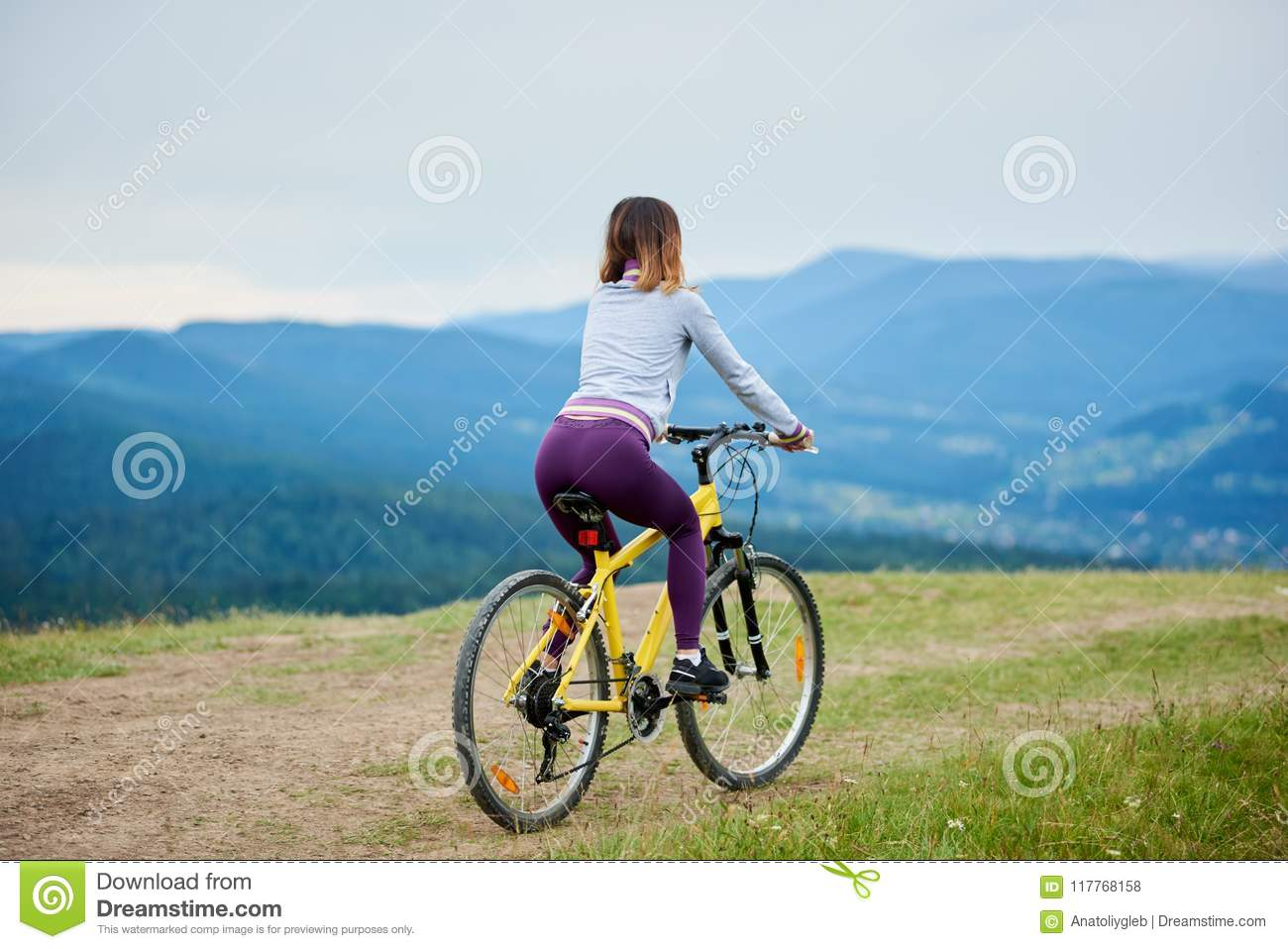 Young Happy Woman Cycling On Mountain Bike At Summer Day