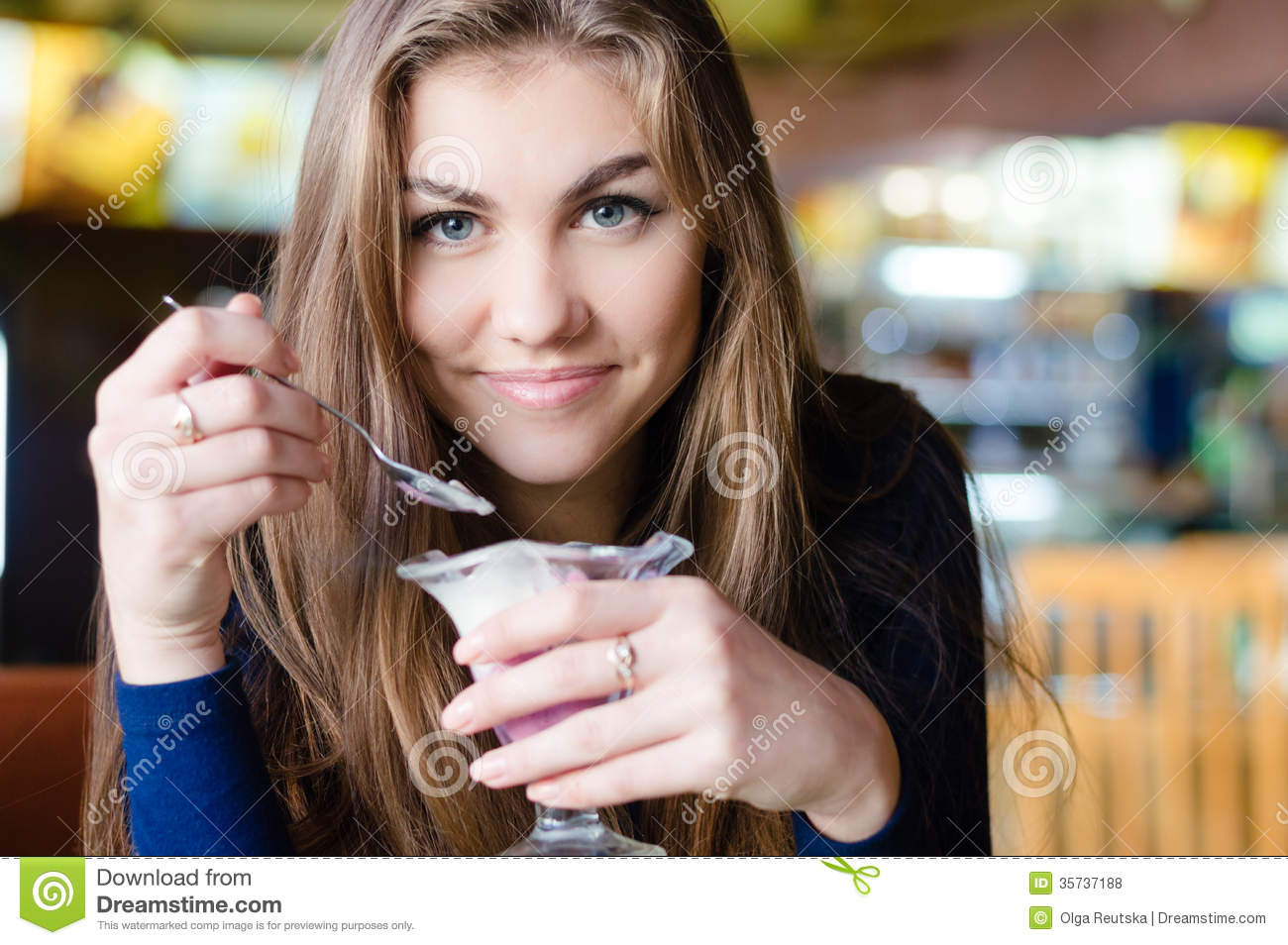 Young happy woman eating ice cream in cafe