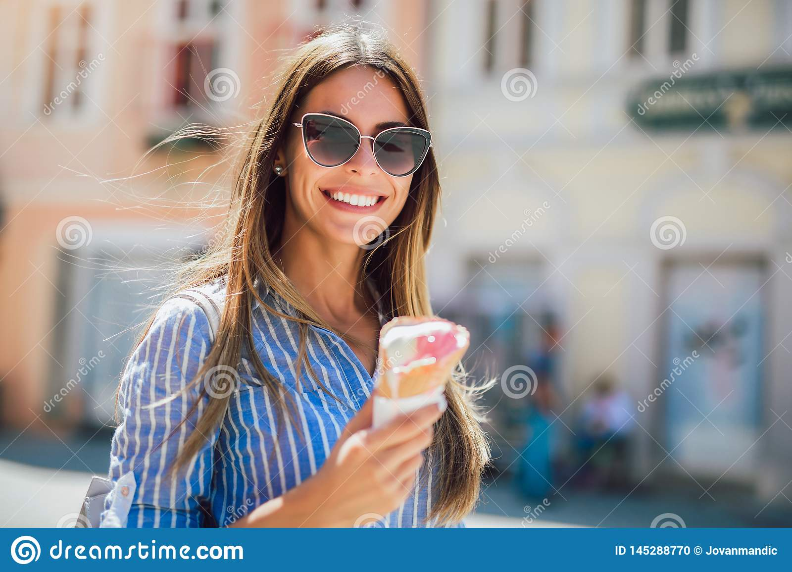 Young happy woman eating ice-cream, outdoor
