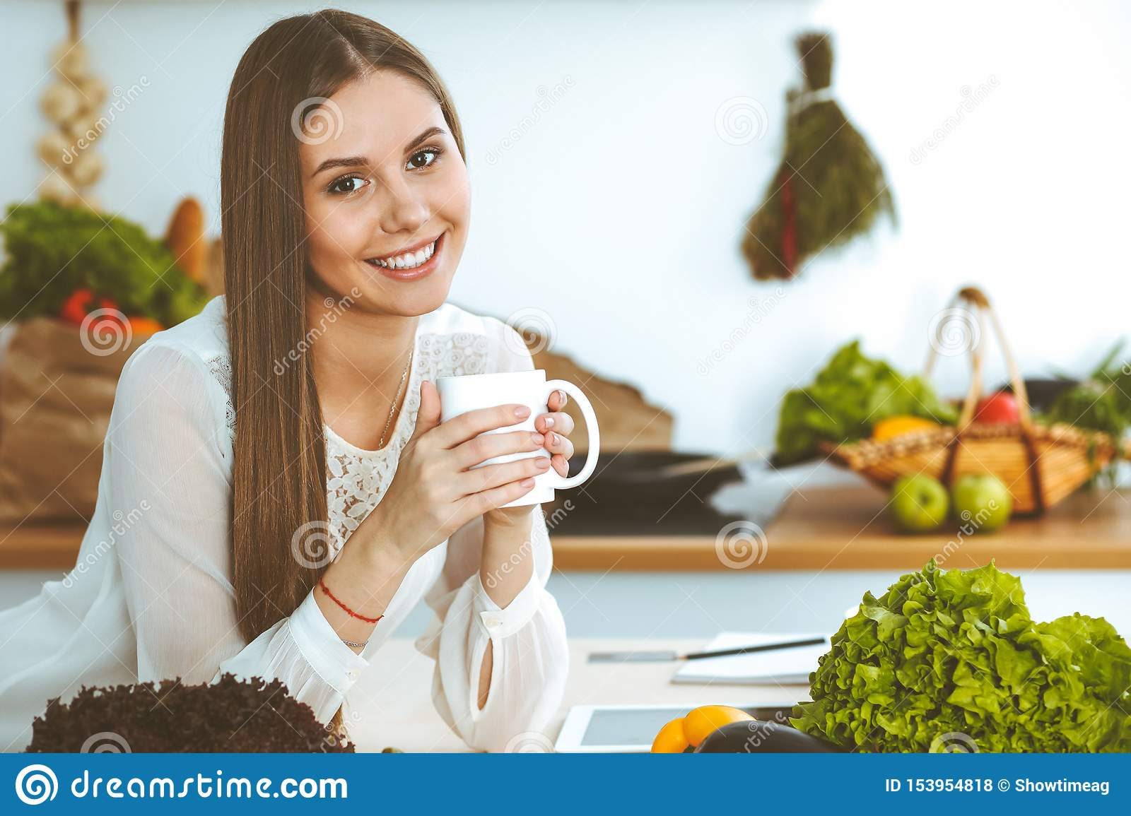 Young happy woman is holding white cup and looking at the camera while sitting at wooden table in the kitchen among
