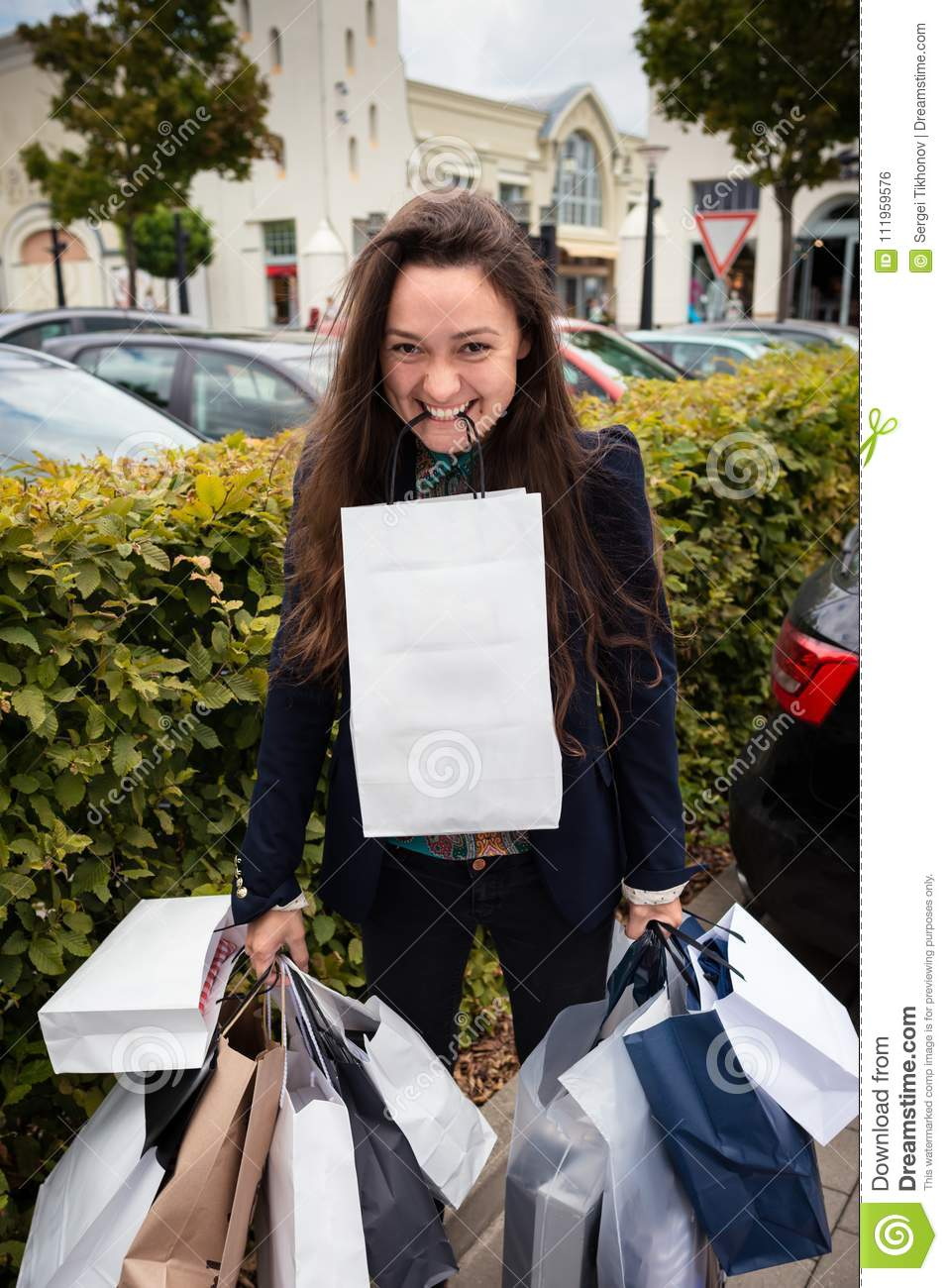 Young happy woman holds many shopping bags in tooth and hands