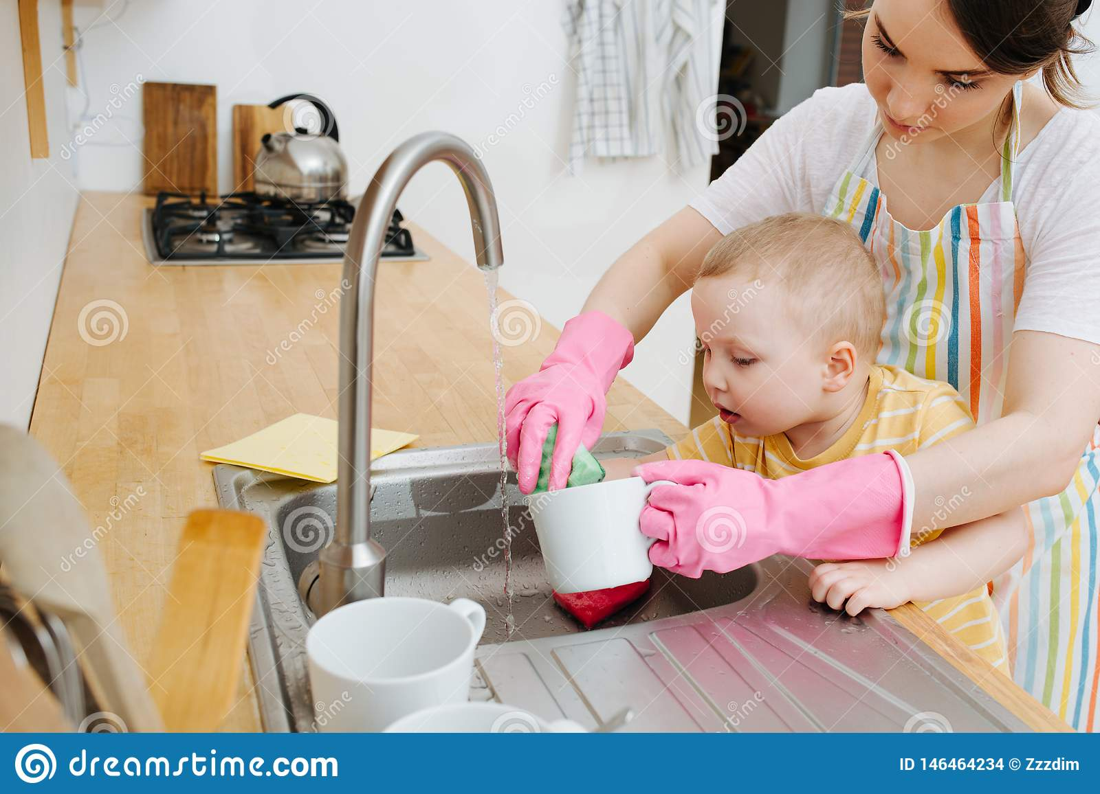 Young happy woman in a kitchen is washing cups and dishes. Her little son helps