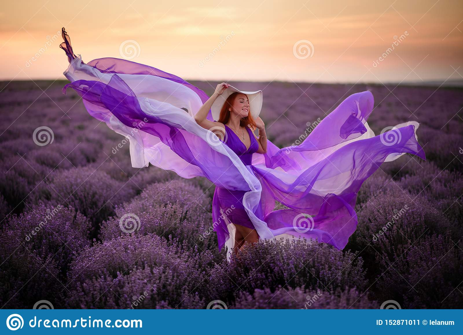 Young happy woman in luxurious purple dress standing in lavender field