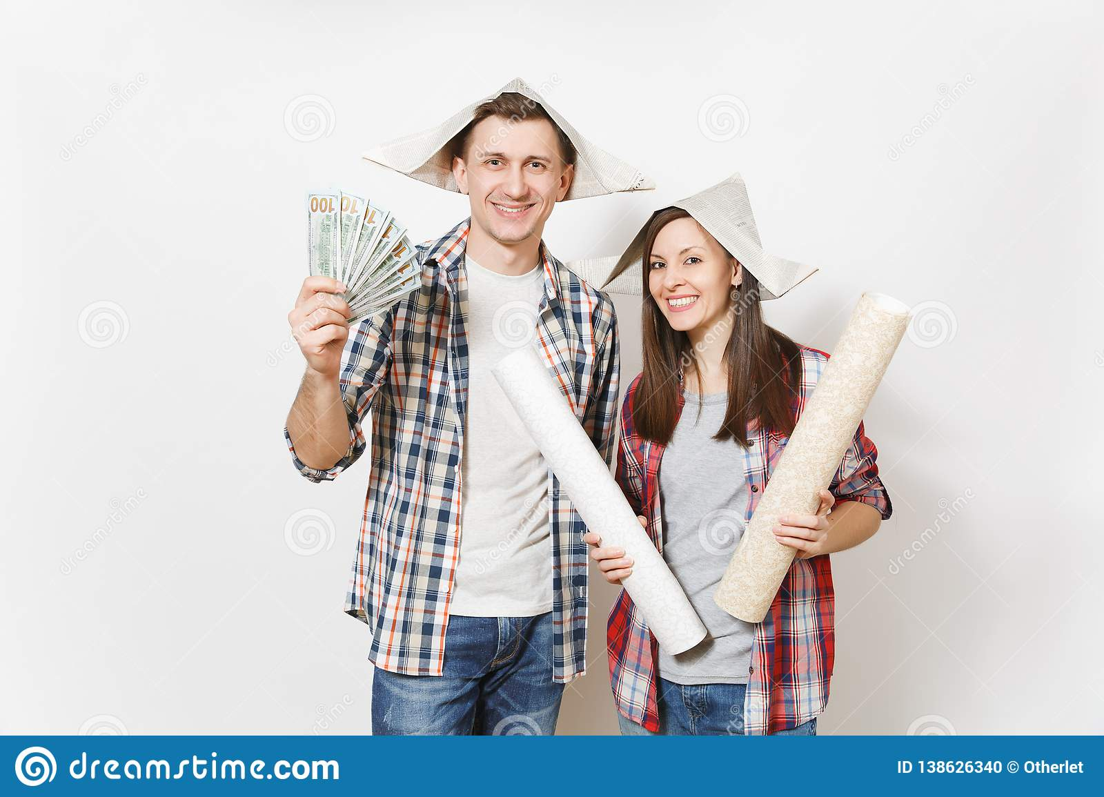 Young happy woman, man in casual clothes holding bundle of dollars, cash money and wallpaper roll. Couple isolated on