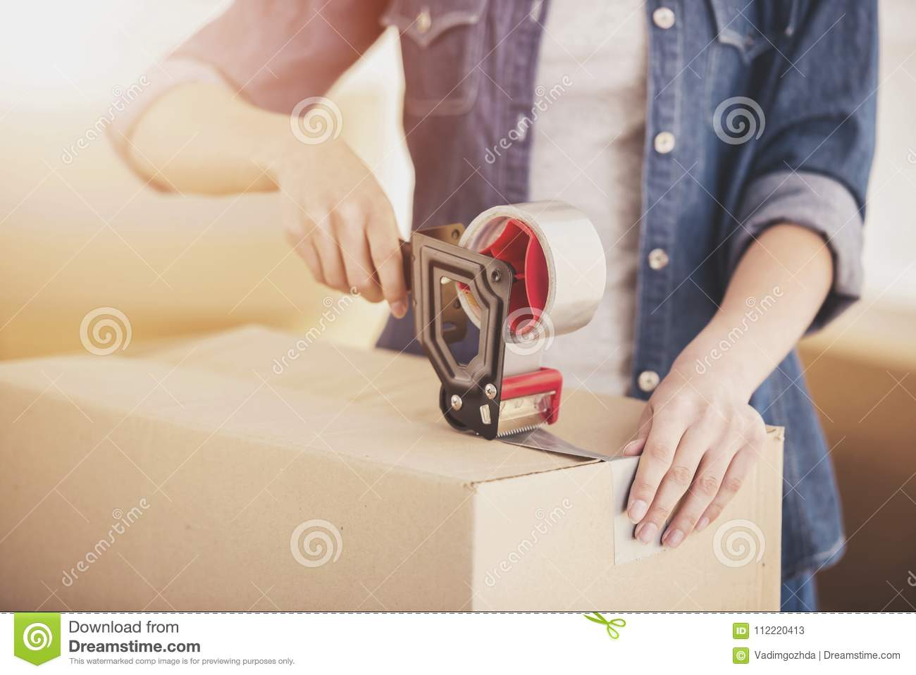 The young happy woman packing boxes. Moving, purchase of new habitation