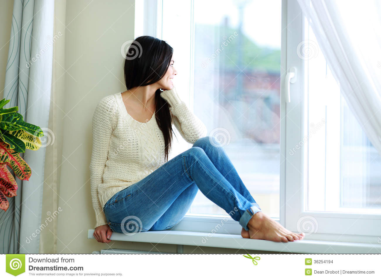young happy woman sitting on a window sill stock images