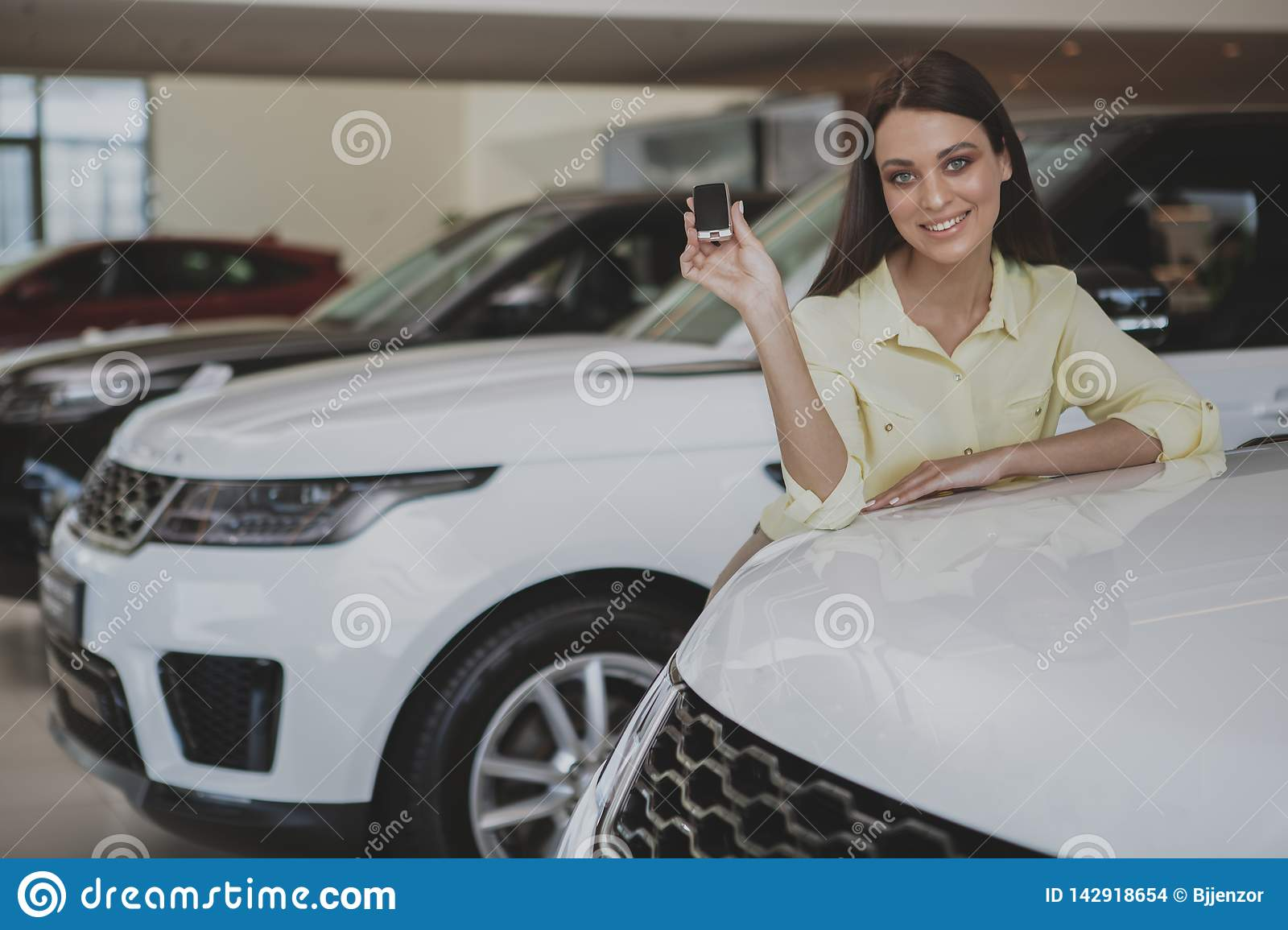 Happy woman holding car keys to her new automobile