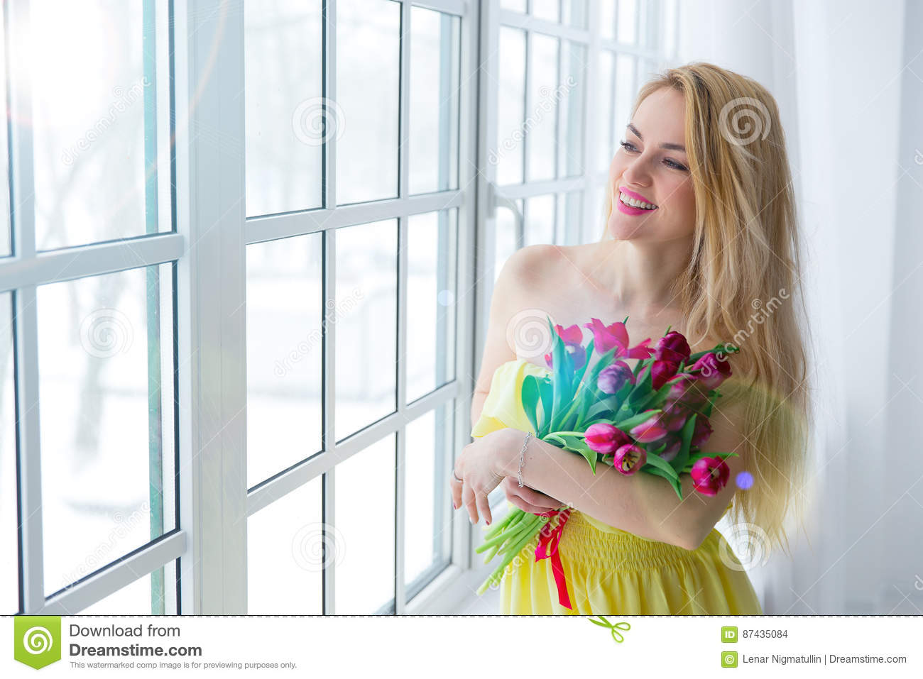 Young happy woman smiling with tulip bunch in yellow dress. 8 march international womens day.