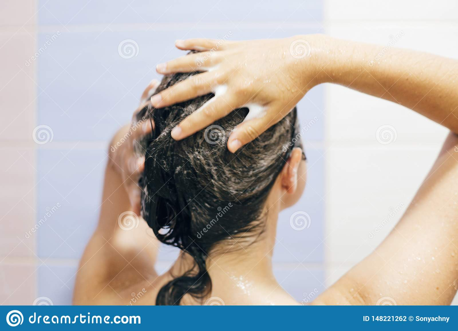 Young happy woman washing her hair with shampoo, hands with foam closeup. Back of beautiful brunette girl taking shower and