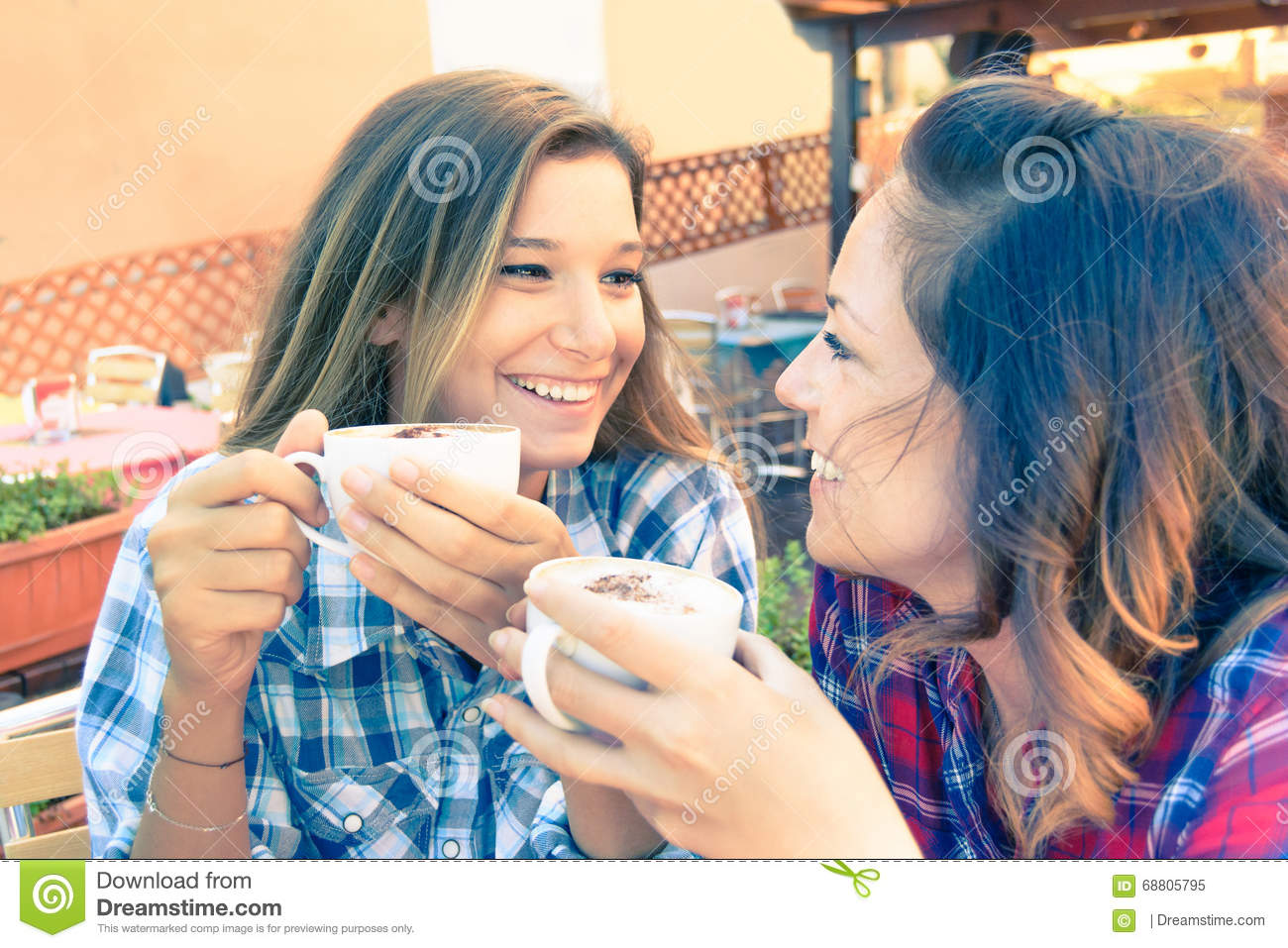 Young hipster best friends having fun talking about gossip during breakfast in bar - Concept of daily moments life and technology