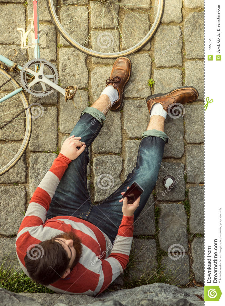 Young Hipster Man Sitting And Using Cellphone Shot From Aerial View