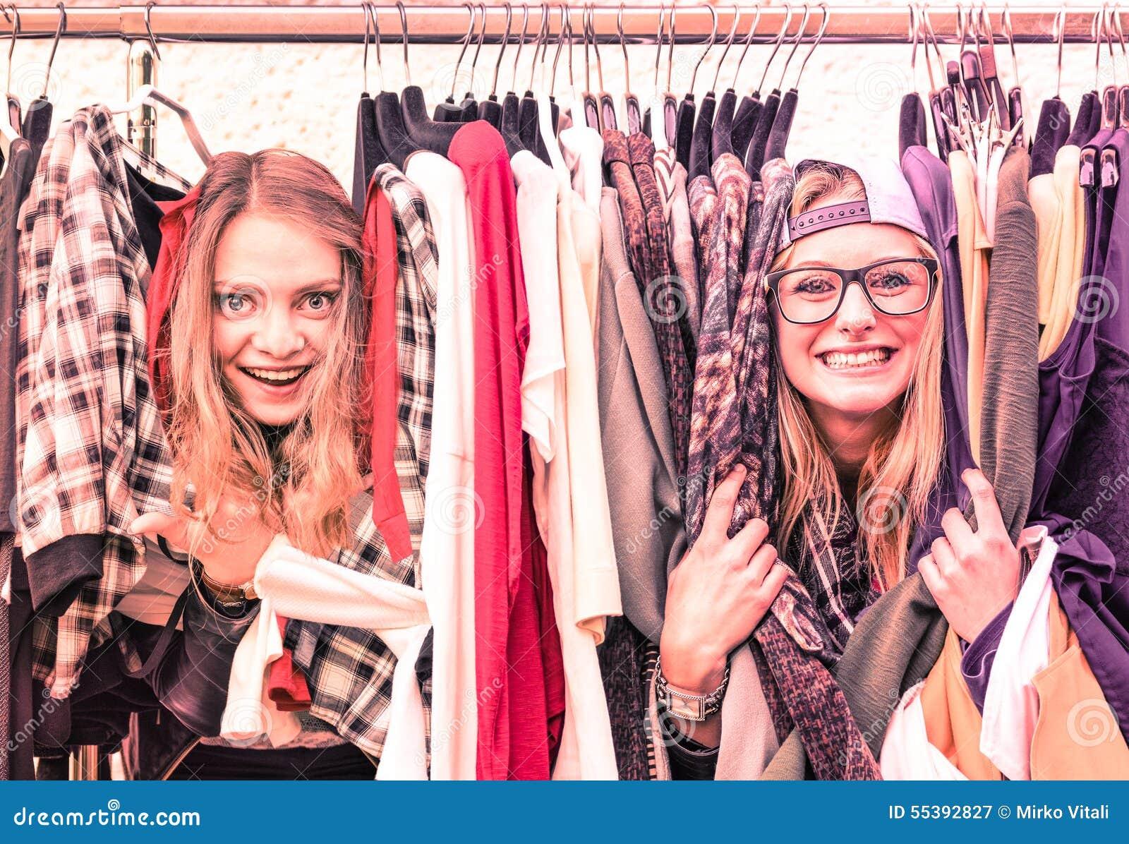 Young hipster women at clothes flea market - Best friends fun