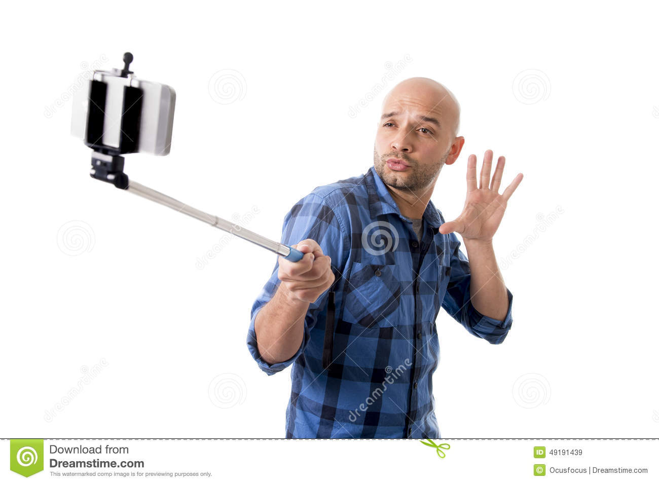 young hispanic man in casual shirt having fun shooting mobile phone selfie picture holding stick. Black Bedroom Furniture Sets. Home Design Ideas