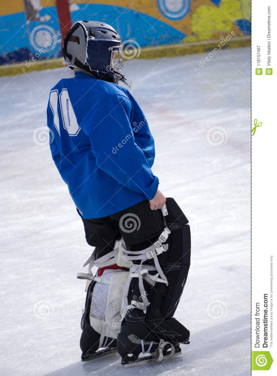 Young Hockey Goalie Poses Without Her Face Mask On A Black