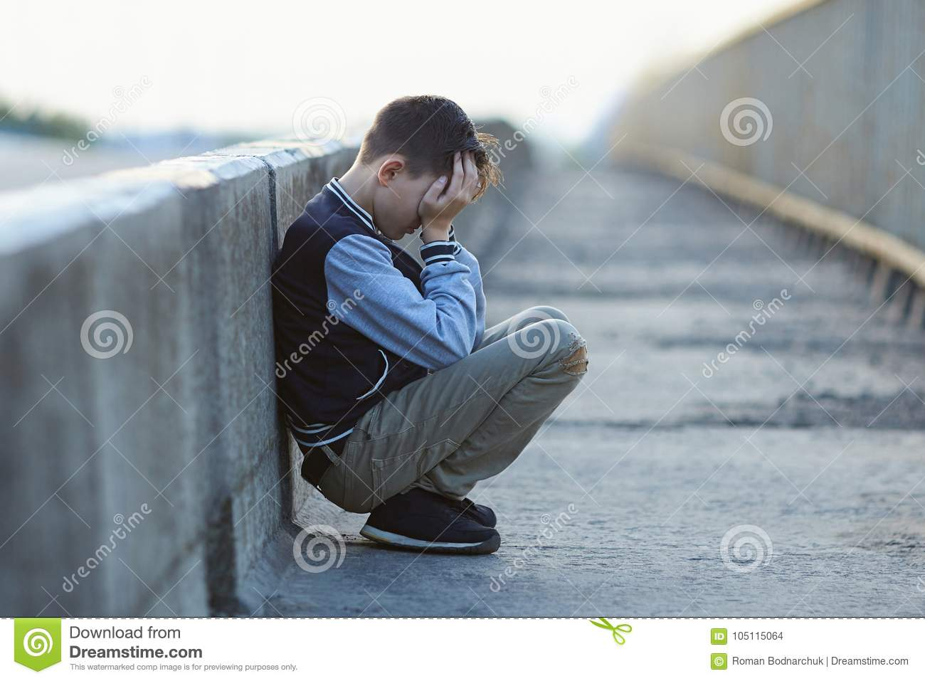 Young homeless boy crying on the bridge