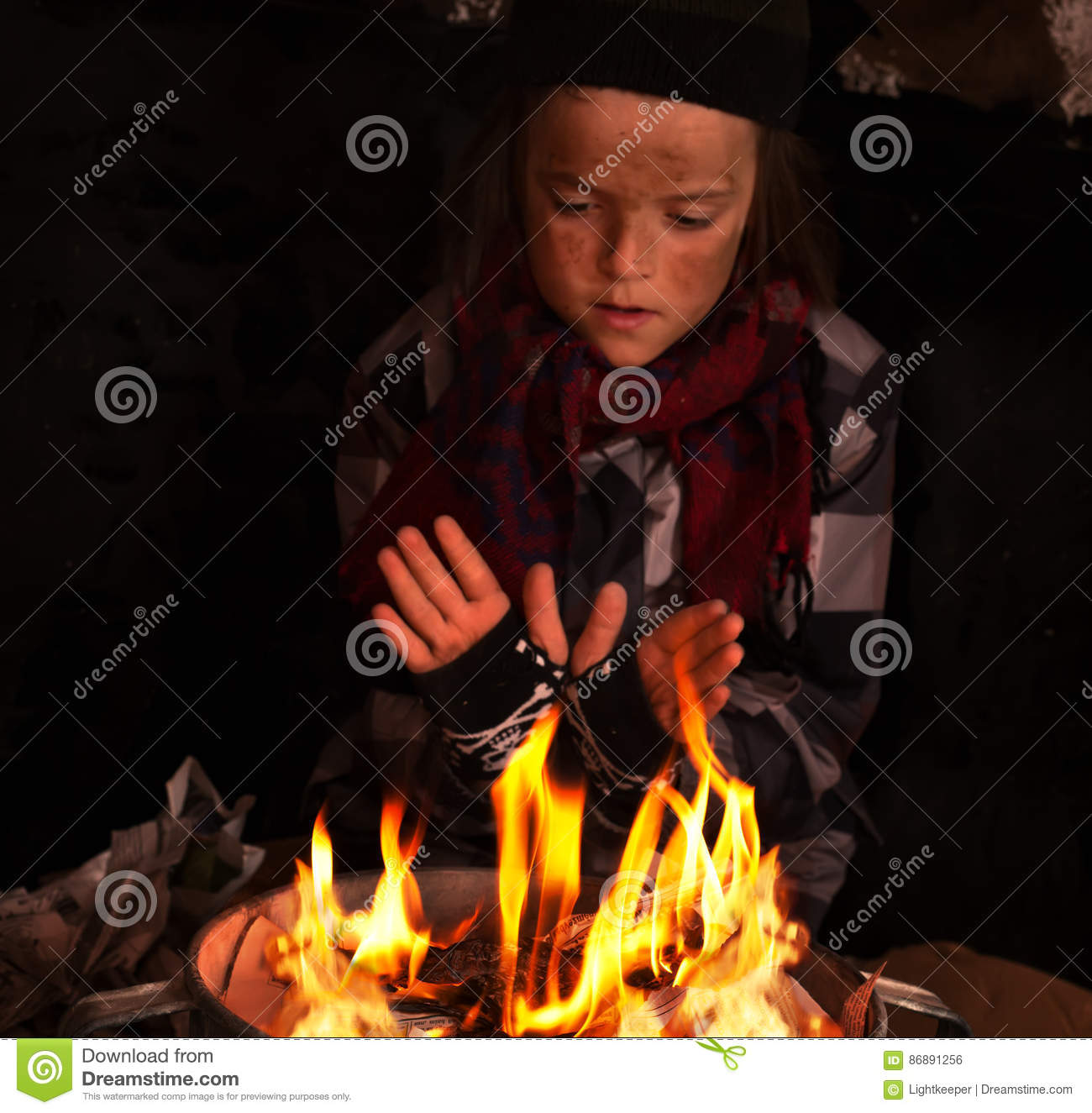 Young homeless boy warming by the newspapers fire