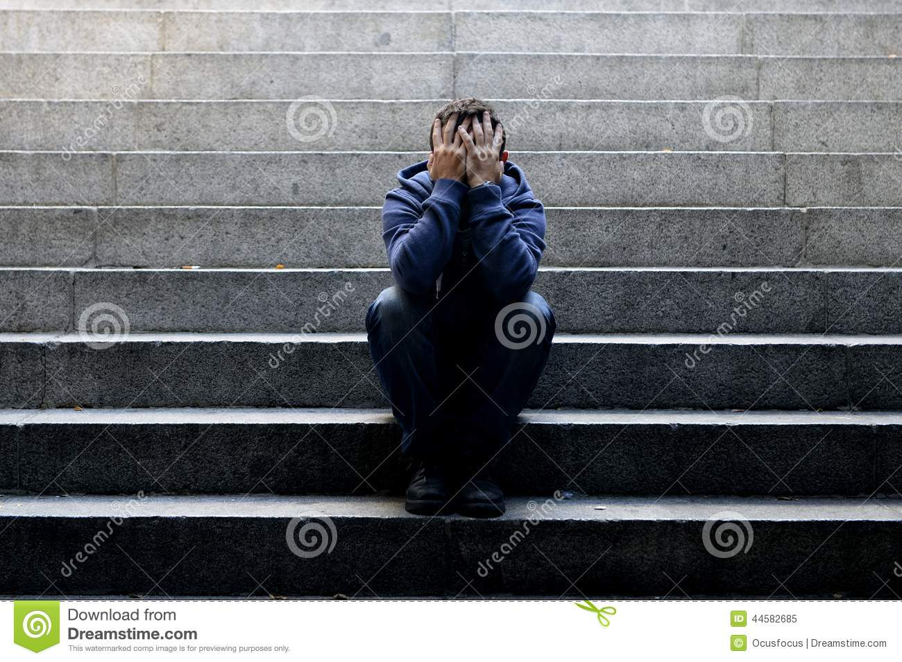 Young homeless man lost job sitting in depression on ground street concrete stairs