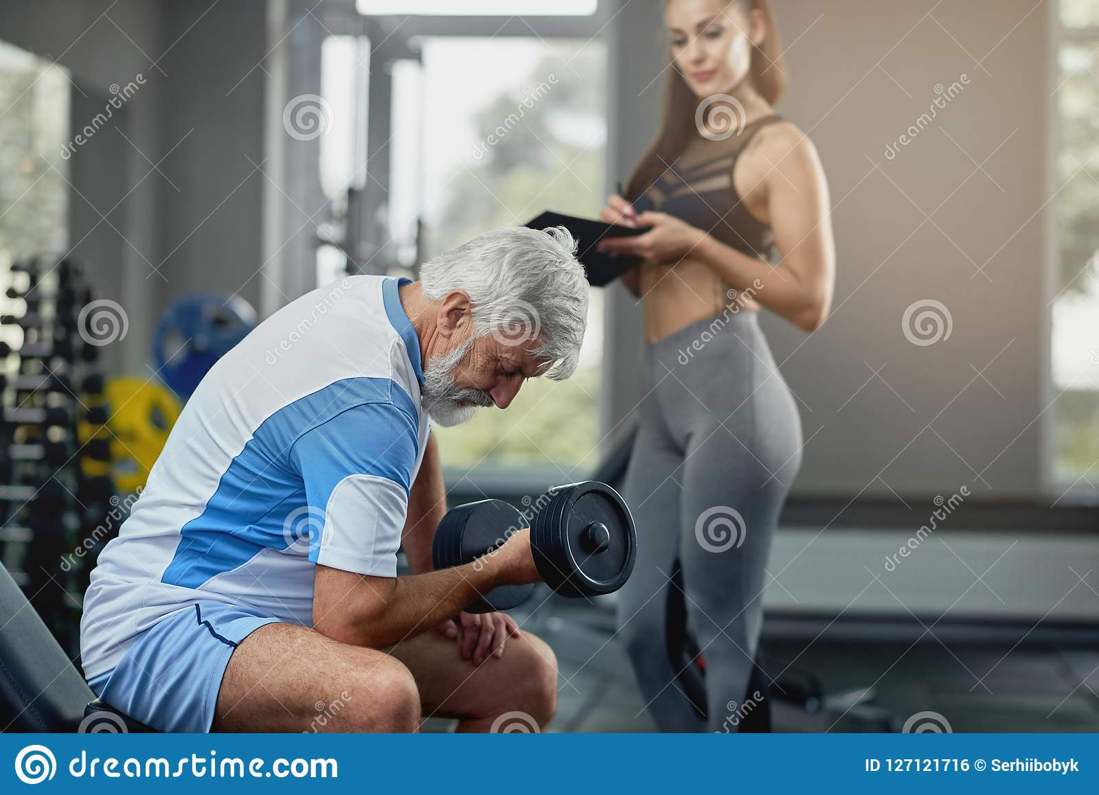 Young Hot Female Personal Trainer Supporting Senior Gray Man