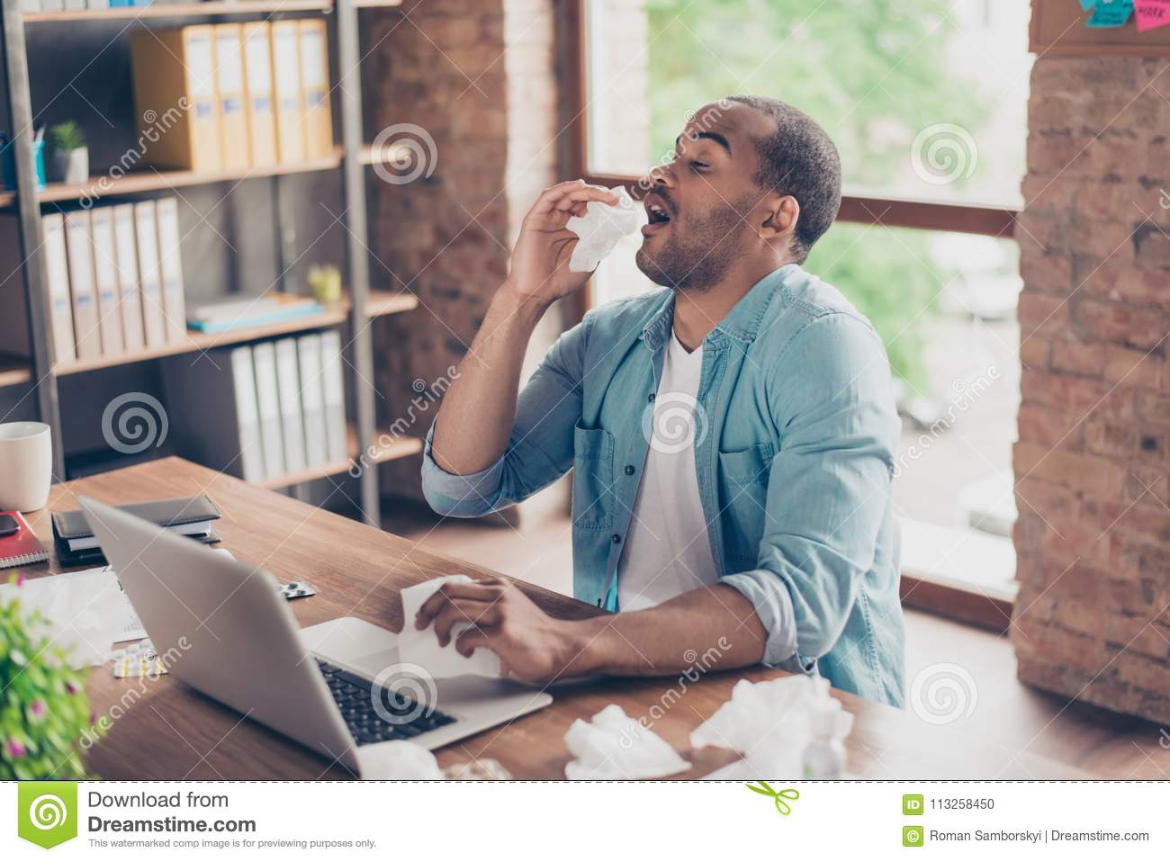 Young ill afro student is sneezing at work place in modern office, a lot of paper napkins on desktop and in his arm