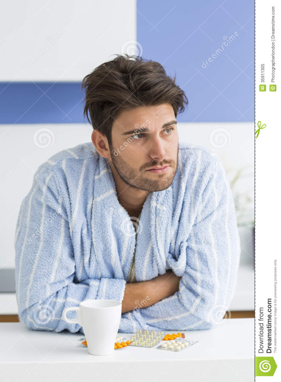 Young Ill Man With Coffee Mug And Medicine Leaning On