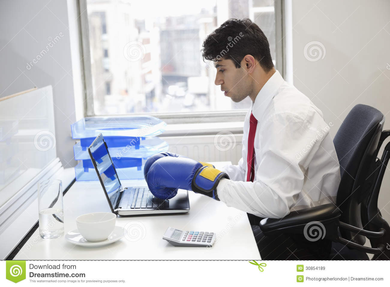 Young Indian Businessman Wearing Boxing Gloves While Using