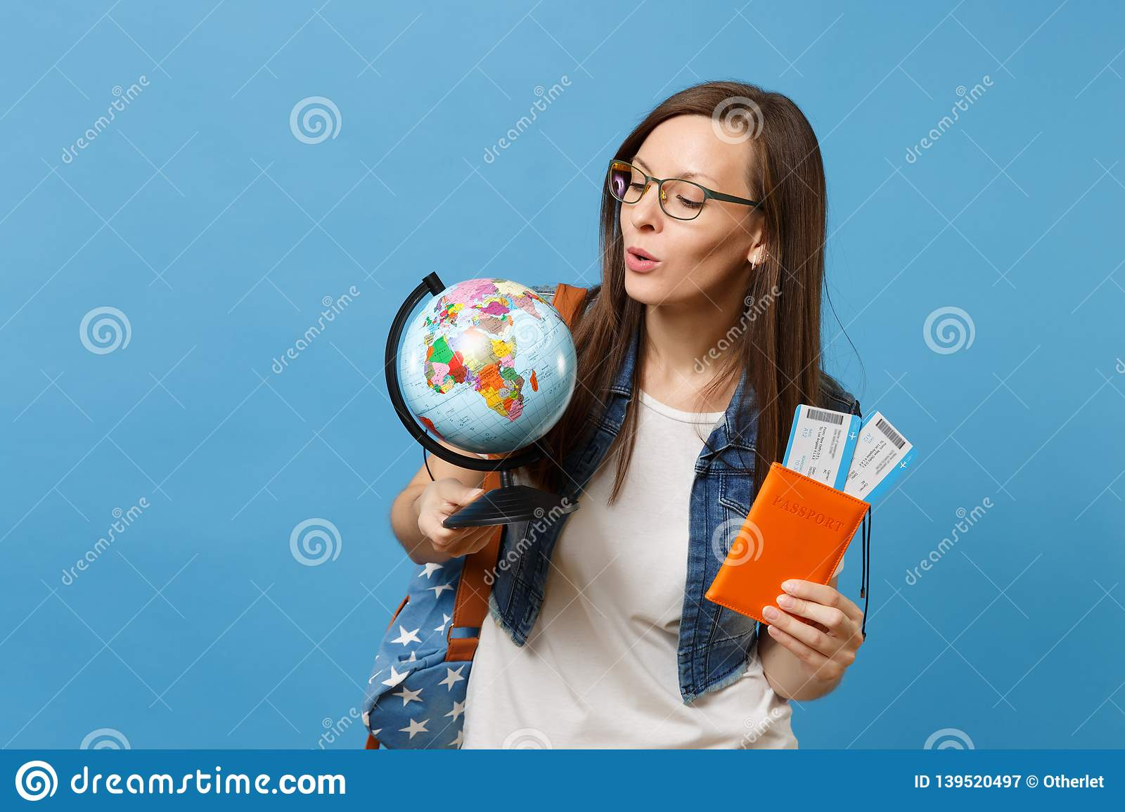 Young interested woman student in glasses looking on world glove holding passport, boarding pass tickets isolated on