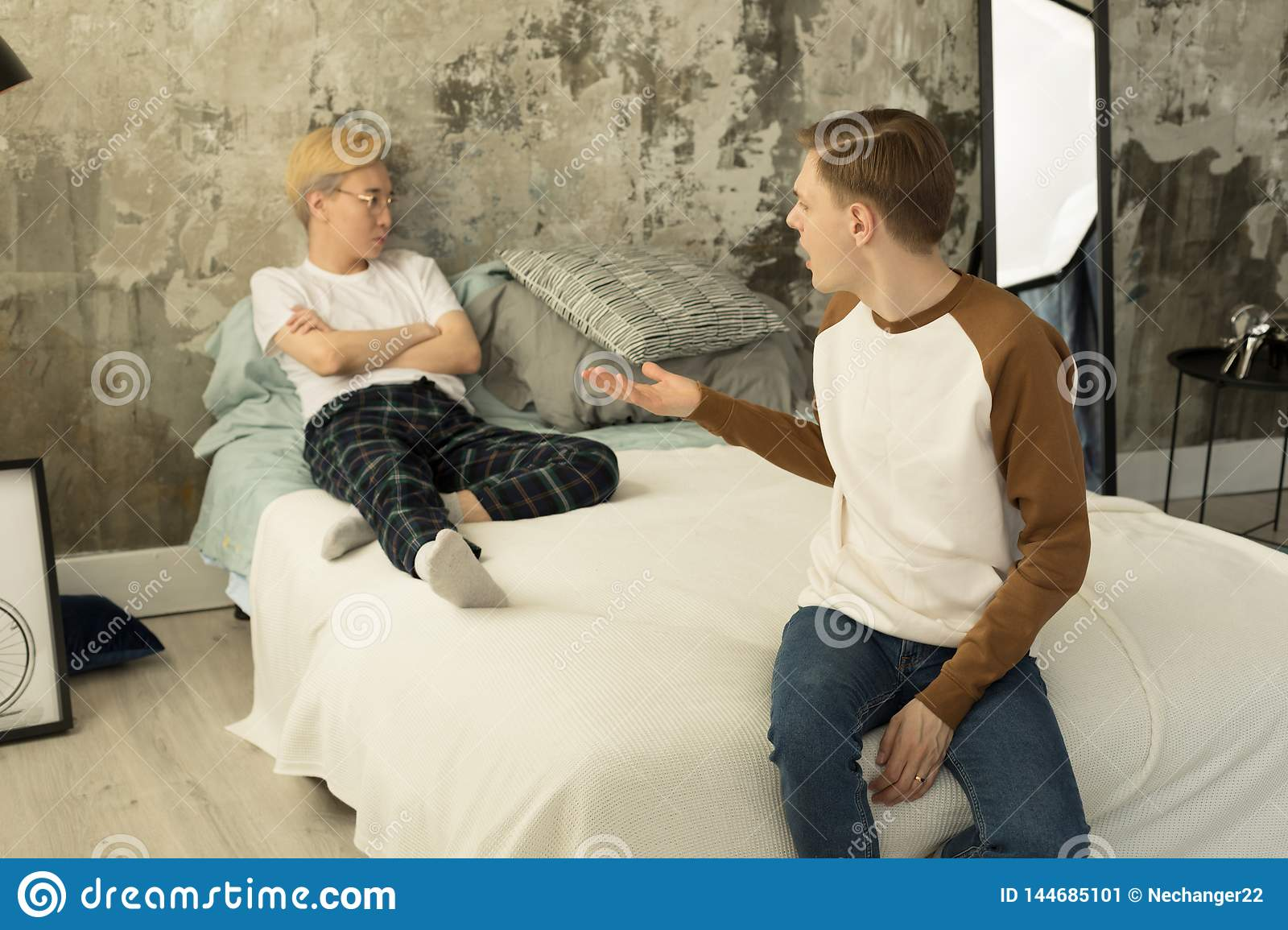 Young international gay couple in quarrel at home in bedroom