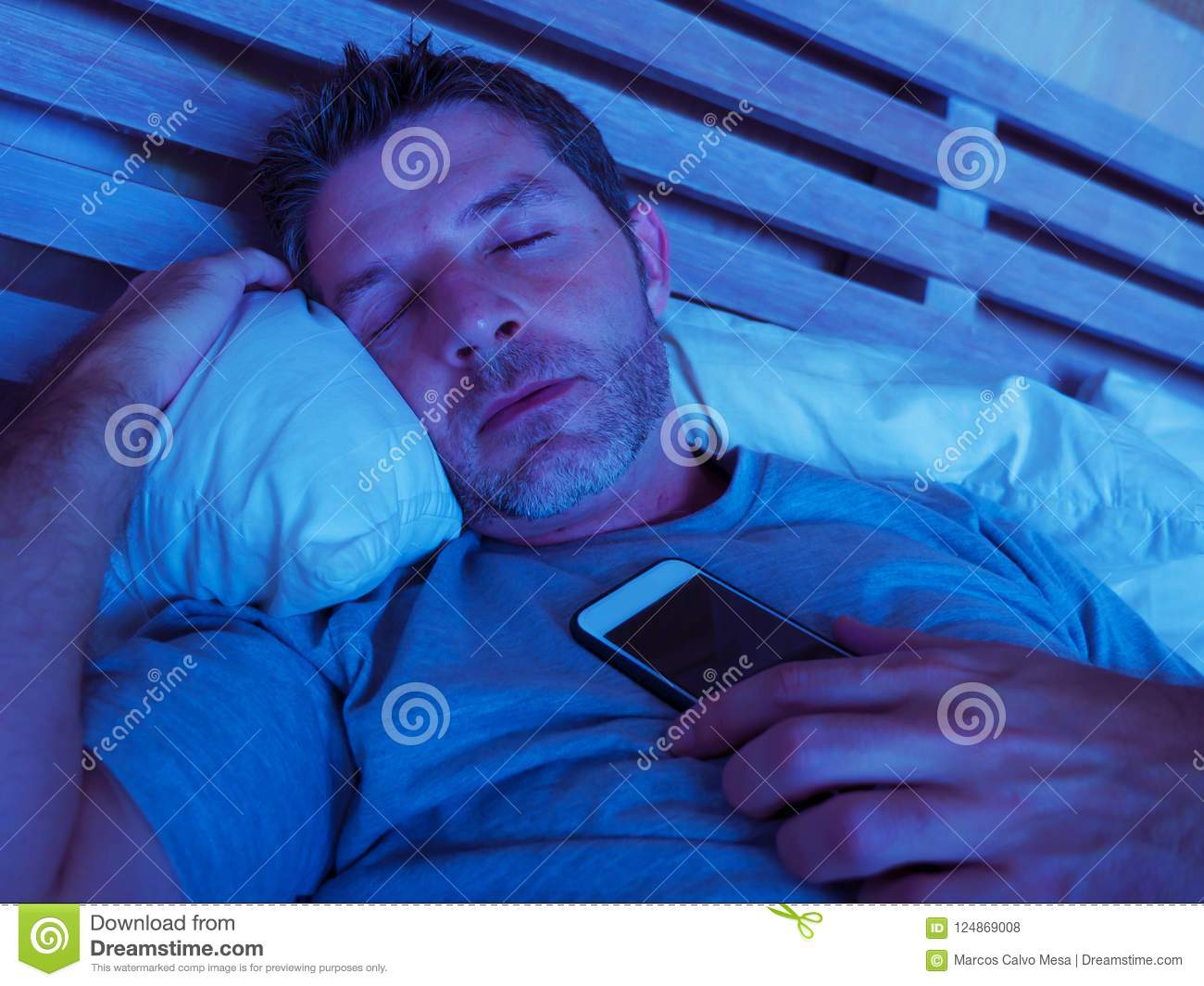 Young internet addict man sleeping on bed holding mobile phone in his hand at night in smartphone and social media network overuse