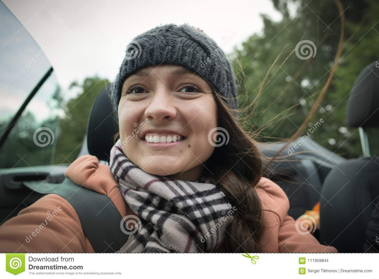 A young joyful girl is traveling in the cabriolet car