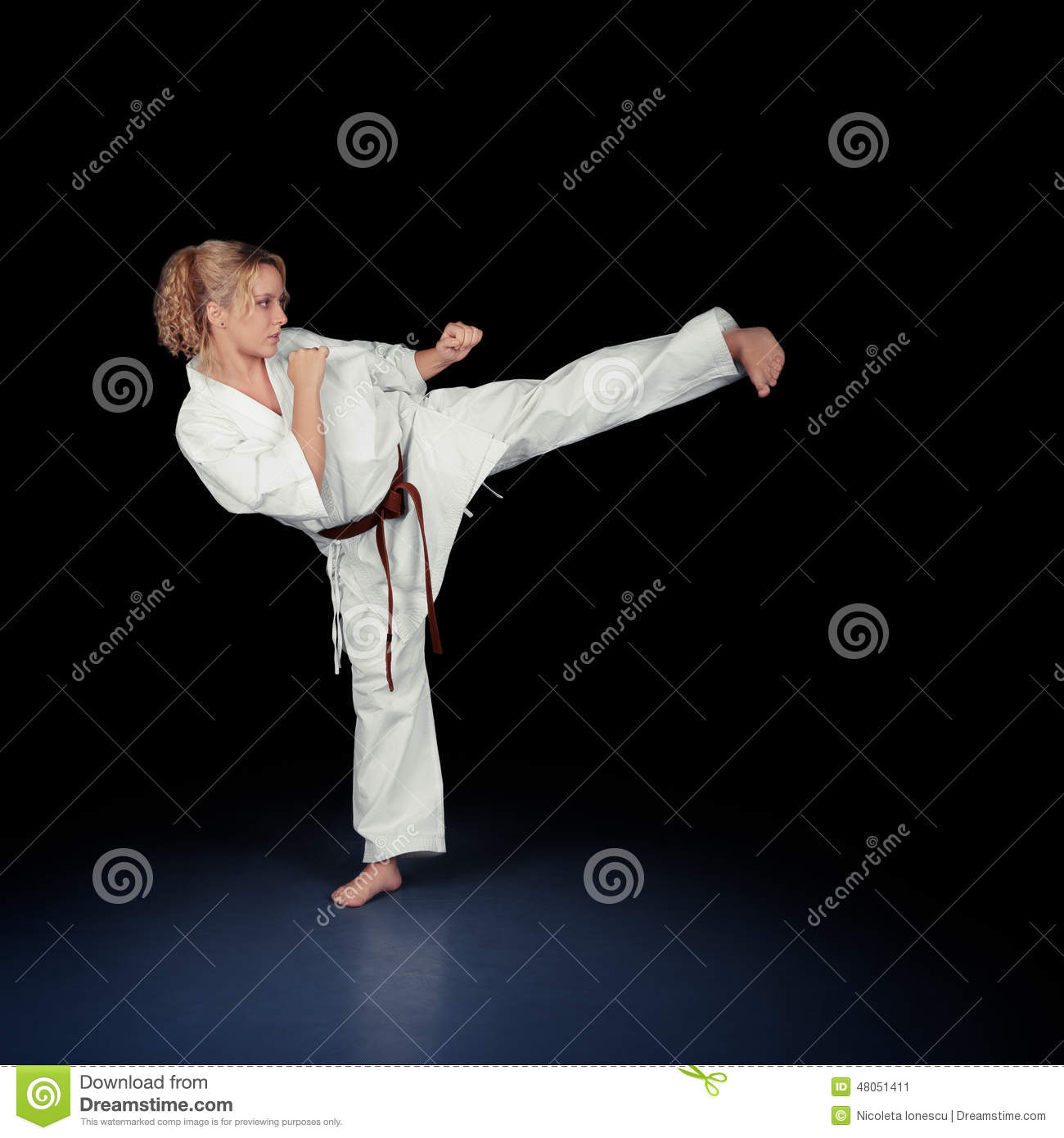 Young Karate Woman In A White Kimono Kicking Stock Photo ...