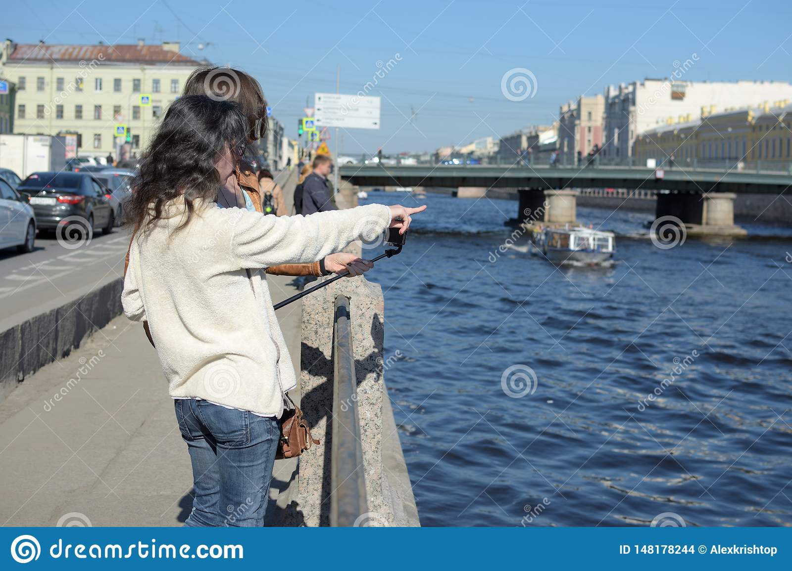 Young ladies tourists in Saint Peteresburg Russia enjoy summer on a sunny day and greet sightseeing boats
