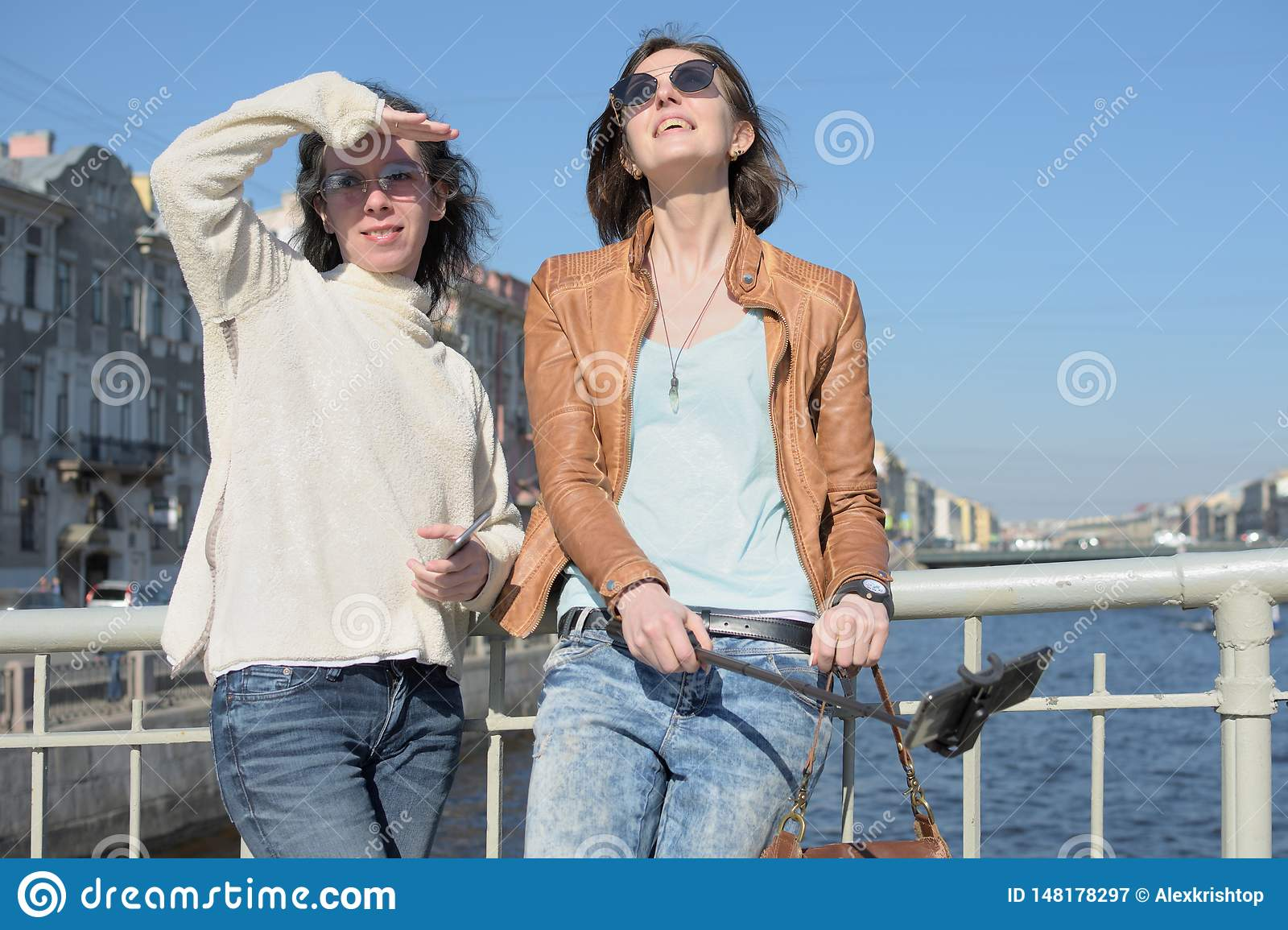 Young ladies tourists in Saint Petersburg Russia take selfies on a wooden bridge in the historical city center