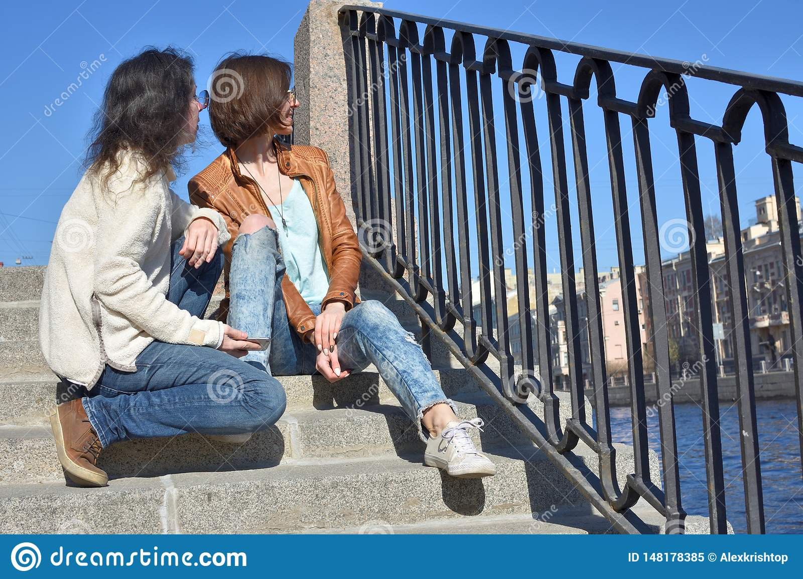 Young ladies tourists sitting together on stair at Fontanka river embankment in Saint Petersburg Russia watching tourist boats on