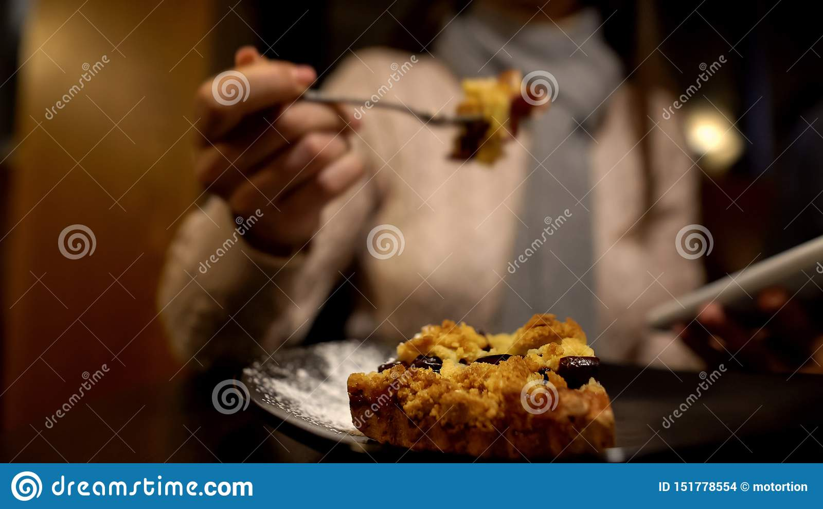Young lady eating tasty pie and using smartphone, enjoying lunch time alone
