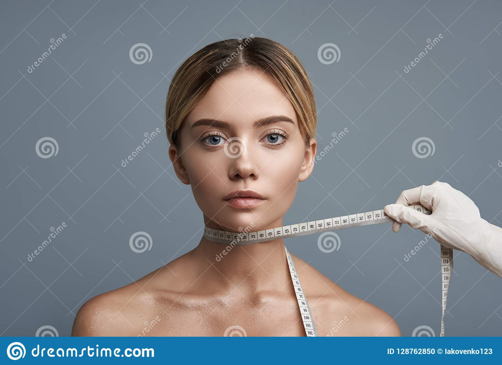 Young lady looking calm while having measuring tape on the neck