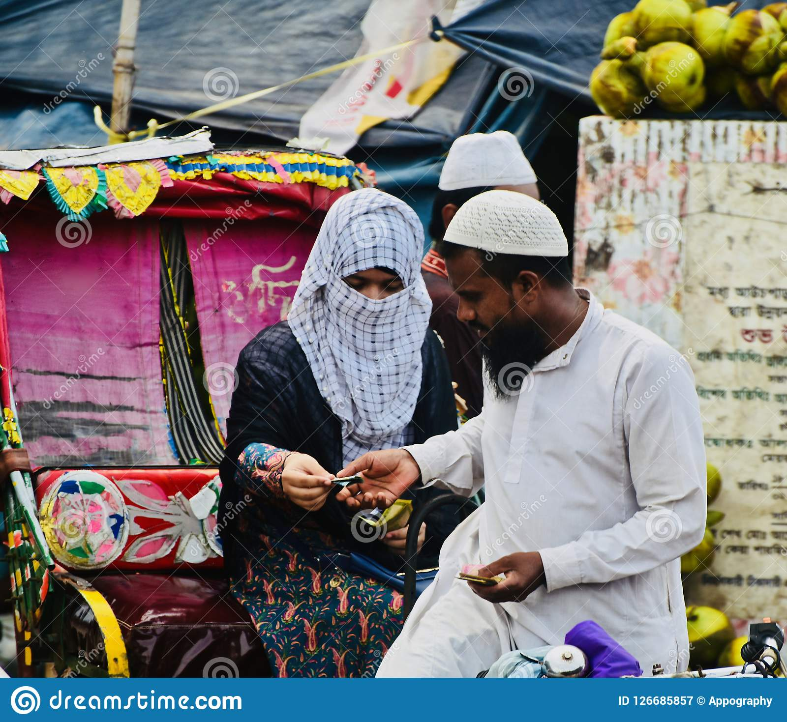 Young muslim lady is paying the ricksha fare to a man unique photo