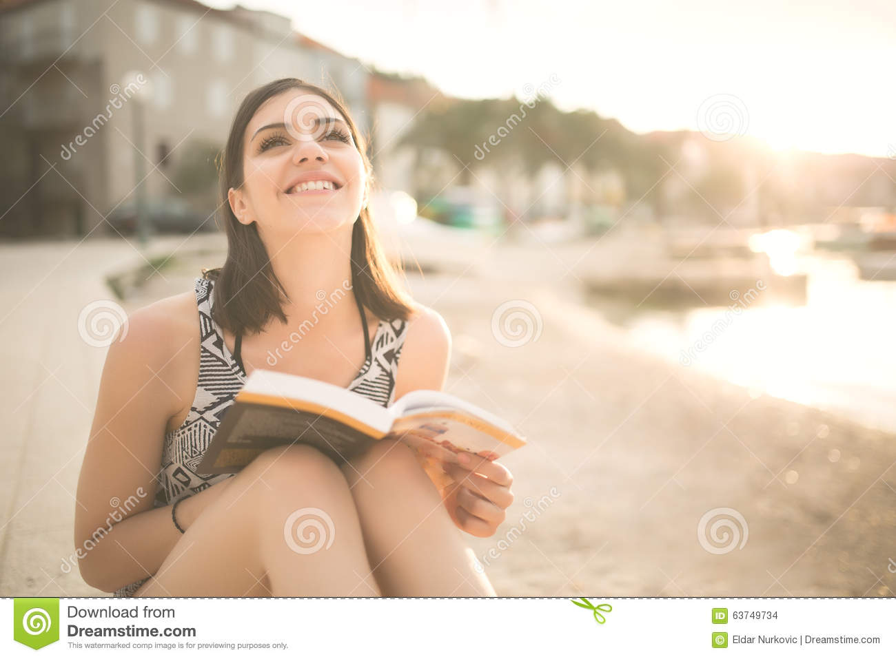Young lady reading a book on a beach at sunset.summer holidays and vacation
