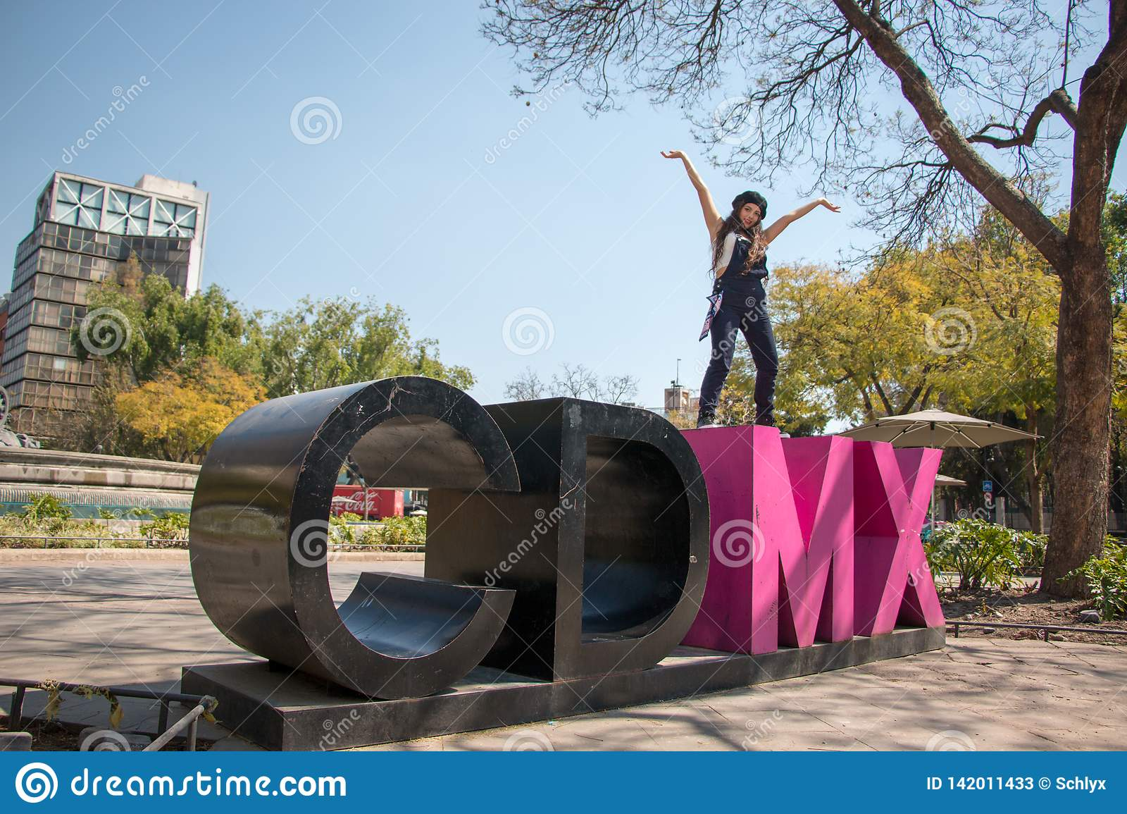 Young lady standing on the CDMX sculpture in la Condesa