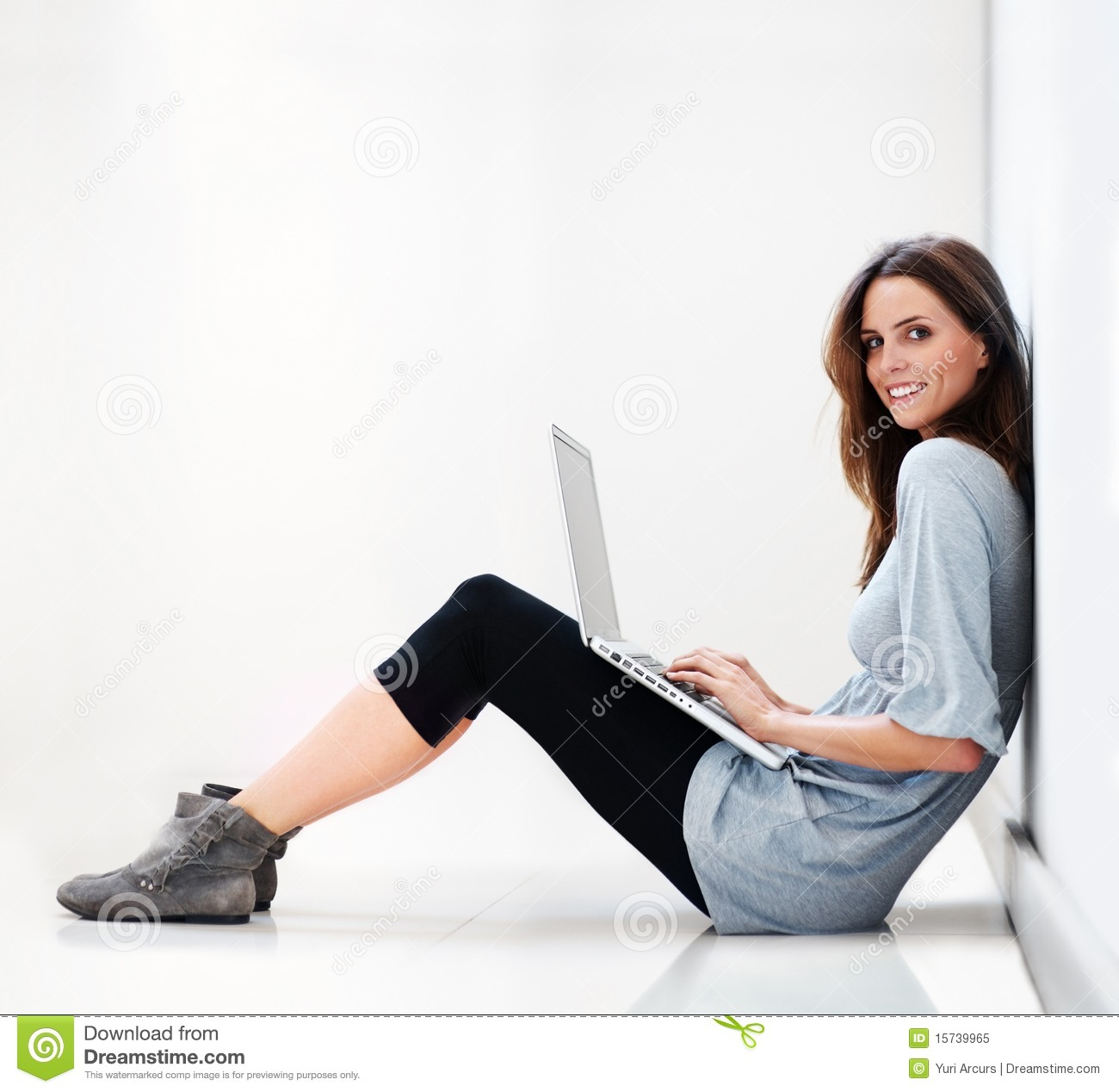 Young Lady Sitting On Floor Working On A Laptop Stock
