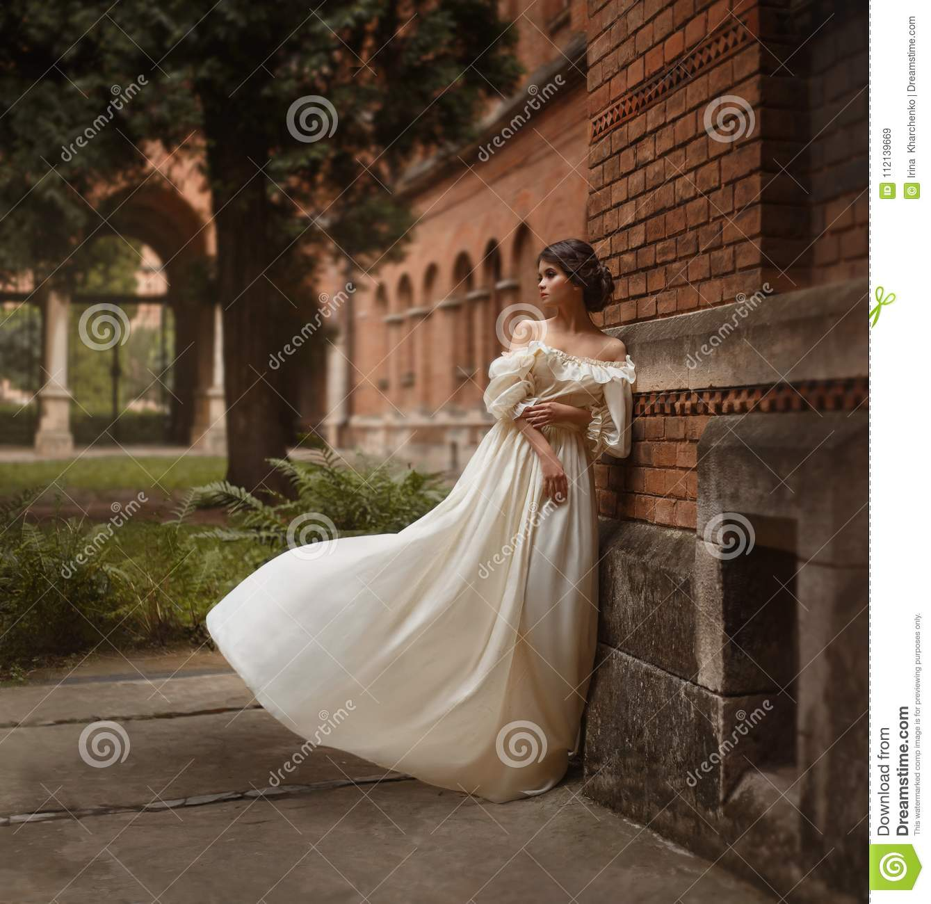 A young lady stands at the wall of an ancient castle looking with hope in the distance. Emotion waiting for the long