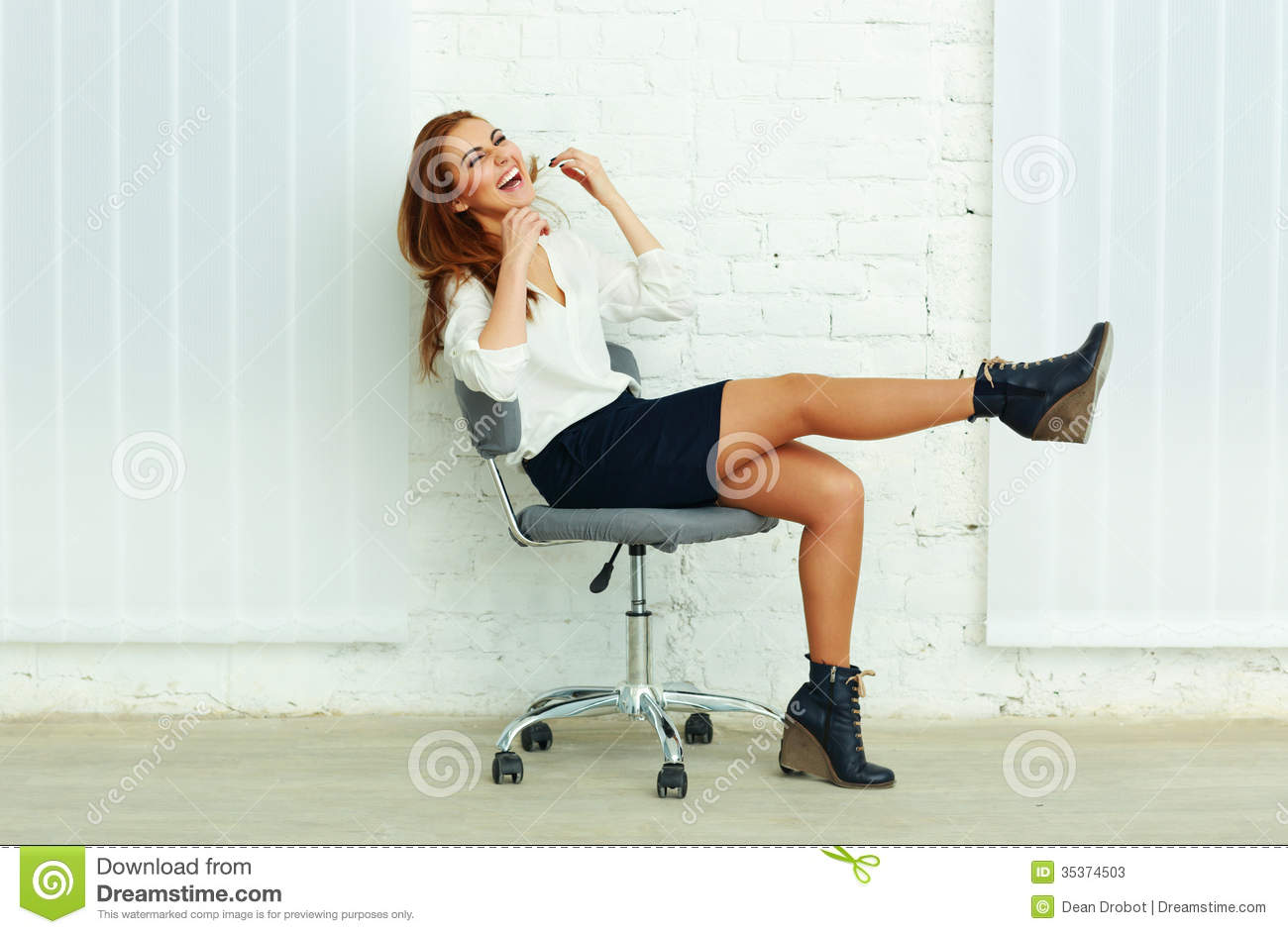 Young Laughing Businesswoman Sitting On The Chair Stock