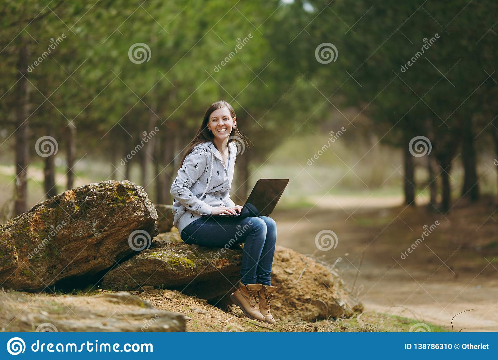 Young laughing successful smart business woman or student in casual clothes sitting on stone using laptop in city park
