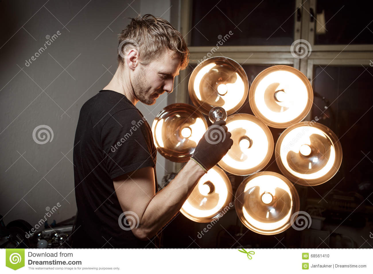 Young light designer looking at old electric bulb