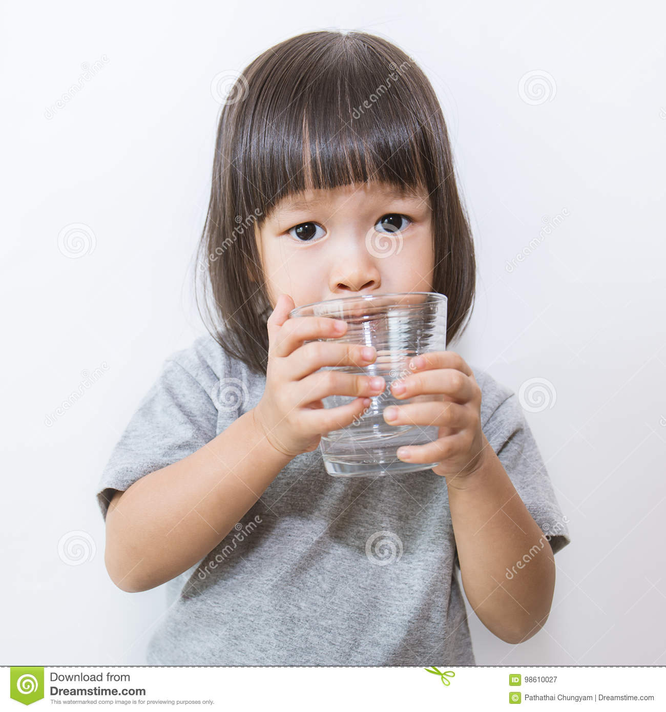 Young Little Asian Girl Drinking A Glass Of Water