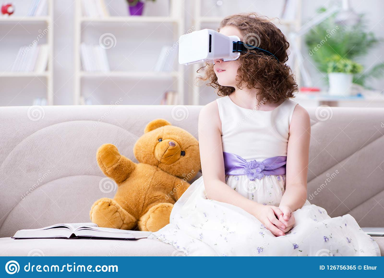 Young Girl Sitting In Virtual Reality Glasses. Before Her