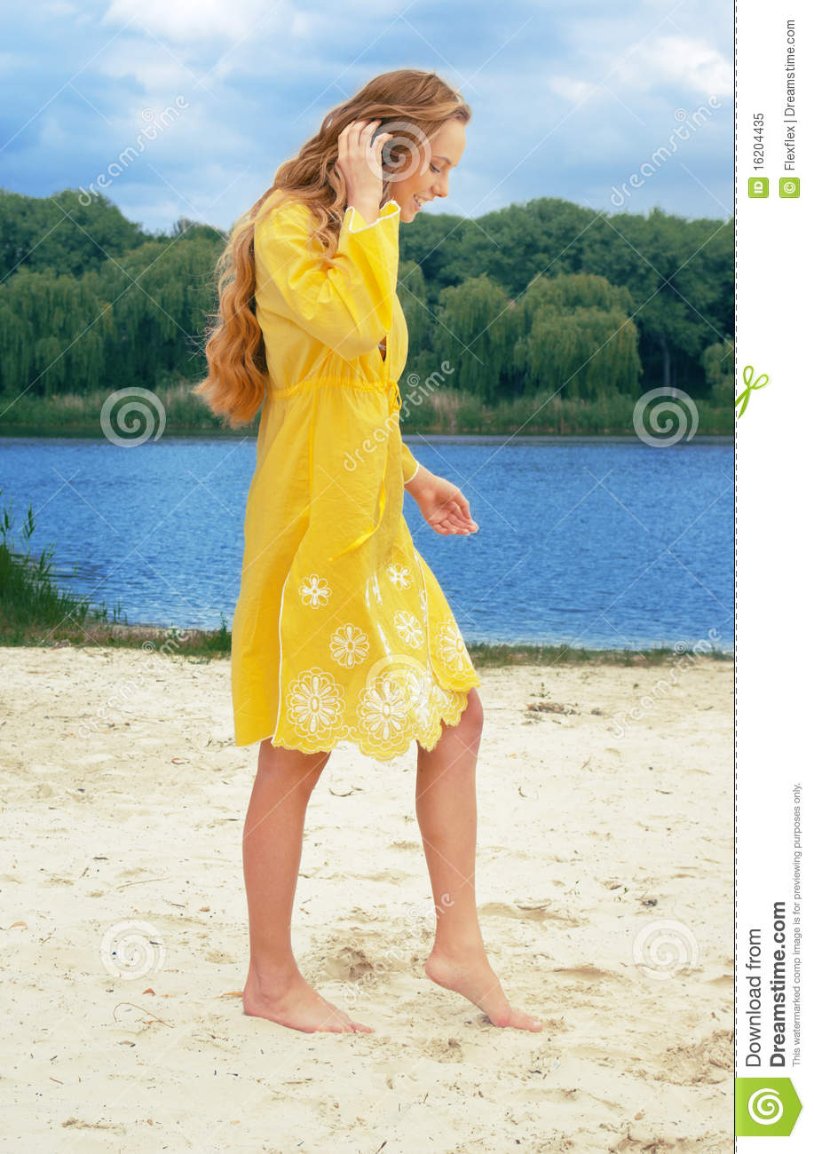 Young long-haired attractive woman in yellow outfi